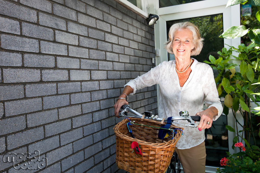 Portrait of happy senior woman with bicycle standing at backyard