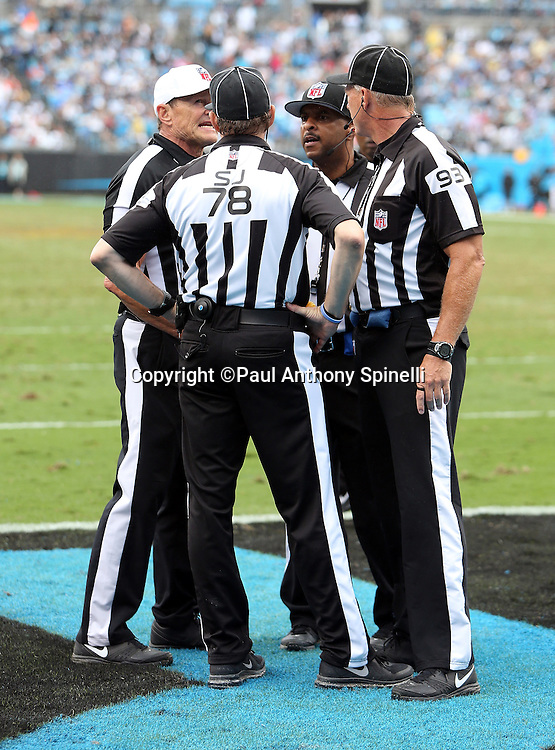 Referee Ed Hochuli (85), side judge Greg Meyer (78), and back judge Scott Helverson (93) meet to discuss a play during the Carolina Panthers 2015 NFL week 3 regular season football game against the New Orleans Saints on Sunday, Sept. 27, 2015 in Charlotte, N.C. The Panthers won the game 27-22. (©Paul Anthony Spinelli)