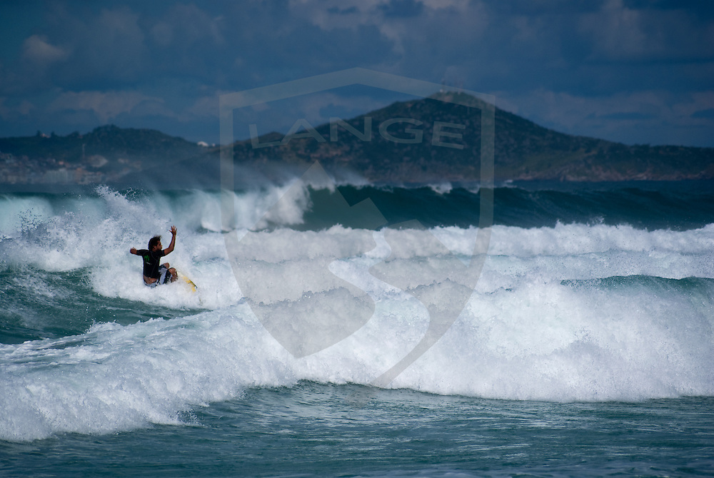 surfer surfing the rough tide with a dramatic mountain landscape behind at cabo frio in rio de janeiro, brazil.