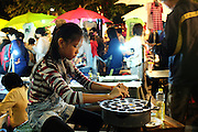 A young girl cracks quail eggs during the Sunday night walking market in Chiang Mai.