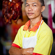 A Chinese butcher stands proudly in front of his barbecue ducks.