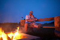 Steve Hollaway snuggles his baby daughter and a glass of wine at a bonfire on the beach near Yachats and Waldport, Oregon.