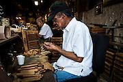 Hispanic men roll cigars in a workshop