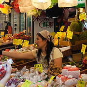 Woman selling fruit and vegetables at street market, Hong Kong