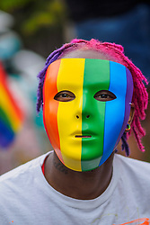 United States, Washington, Seattle Gay Pride Parade, June 28th, 2015. African-American person in rainbow mask.