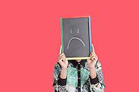 Teenage boy holding sad smiley face sign over pink background