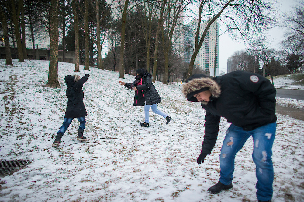 Syrian refugee Nasimi Batal Al Hasan, his brother Ali (right), and his sister Fusie (centre), play in the snow outside of their apartment building in Mississauga, Ontario, Canada, Thursday January 21, 2016.   (Mark Blinch for the BBC)