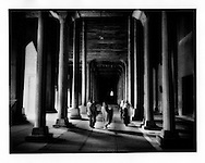 Kashmiri family wends its way through the columns of Jama Masjid (Mosque), Srinigar, Kashmir.