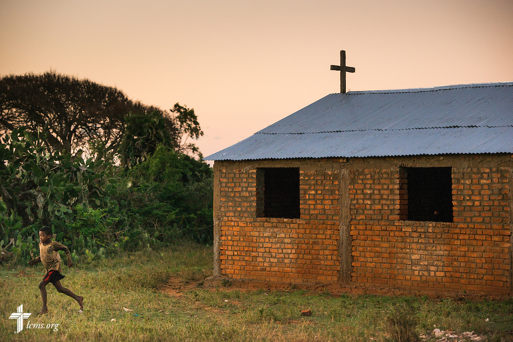 A young boy runs next to his Fiangonana Loterana Malagasy (FLM, Malagasy Lutheran Church) church near Ambovombe, Madagascar, on Monday, Oct. 20, 2014. The tin roof of the church was provided by The Lutheran Church–Missouri Synod. LCMS Communications/Erik M. Lunsford