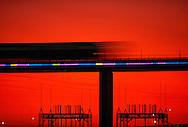 Speeding Miami Metrorail train passing over the Miami River bridge at twilight showing lit Neon Art.