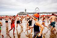 SCHEVENINGEN - Deelnemers aan de traditionele Unox Nieuwjaarsduik rennen de Noordzee in voor een verfrissende duik.  copyright robin utrecht