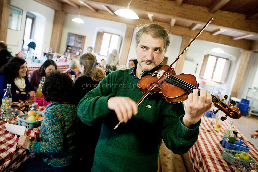 """8 January, 2009. Vicchio, FI, Italy. A worker of Il Forteto plays violin for Simone, Stefano Sarti's son, that turns 23 years old. The Agricultura Cooperativa """"Il Forteto"""" is a lauded producer of traditional Italian cheeses, recognized world over for their pecorino, winning first place of all DOP cheese at Tuttofood International in Milan for their Pecorino Oro Antico, and a gold medal in the Hard DOP Cheese class at 2009's World Cheese Awards in Gran Canaria.<br /> <br /> ©2009 Gianni Cipriano<br /> cell. +1 646 465 2168 (USA)<br /> cell. +39 328 567 7923<br /> gianni@giannicipriano.com<br /> www.giannicipriano.com"""