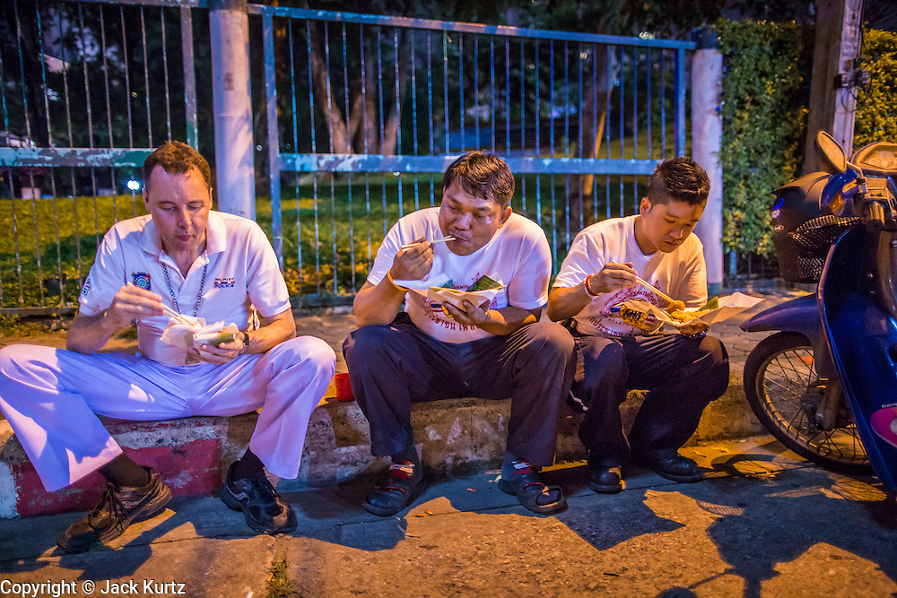 """30 NOVEMBER 2012 - BANGKOK, THAILAND: Medics with the Ruamkatanyu Foundation eat their dinner of """"Pad Thai"""" while they wait for a call near the Ekamai BTS stop during a Friday night shift. The Ruamkatanyu Foundation was started more than 60 years ago as a charitable organisation that collected the dead and transported them to the nearest facility. Crews sometimes found that the person they had been called to collect wasn't dead, and they were called upon to provide emergency medical care. That's how the foundation medical and rescue service was started. The foundation has 7,000 volunteers nationwide and along with the larger Poh Teck Tung Foundation, is one of the two largest rescue services in the country. The volunteer crews were once dubbed Bangkok's """"Body Snatchers"""" but they do much more than that now.    PHOTO BY JACK KURTZ"""