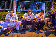 "30 NOVEMBER 2012 - BANGKOK, THAILAND: Medics with the Ruamkatanyu Foundation eat their dinner of ""Pad Thai"" while they wait for a call near the Ekamai BTS stop during a Friday night shift. The Ruamkatanyu Foundation was started more than 60 years ago as a charitable organisation that collected the dead and transported them to the nearest facility. Crews sometimes found that the person they had been called to collect wasn't dead, and they were called upon to provide emergency medical care. That's how the foundation medical and rescue service was started. The foundation has 7,000 volunteers nationwide and along with the larger Poh Teck Tung Foundation, is one of the two largest rescue services in the country. The volunteer crews were once dubbed Bangkok's ""Body Snatchers"" but they do much more than that now.    PHOTO BY JACK KURTZ"