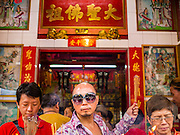 "19 FEBRUARY 2015 - BANGKOK, THAILAND: People pray at a shrine in Bangkok's Chinatown on Chinese New Year. 2015 is the Year of Goat in the Chinese zodiac. The Goat is the eighth sign in Chinese astrology and ""8"" is considered to be a lucky number. It symbolizes wisdom, fortune and prosperity. Ethnic Chinese make up nearly 15% of the Thai population. Chinese New Year (also called Tet or Lunar New Year) is widely celebrated in Thailand, especially in urban areas that have large Chinese populations.    PHOTO BY JACK KURTZ"