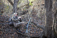 DEER HUNTER WEARING REALTREE AP CAMOUFLAGE GLASSES WITH BINOCULARS WHILE A THOMPSON CENTER OMEGA MUZZLELOADER LIES BESIDE HIM