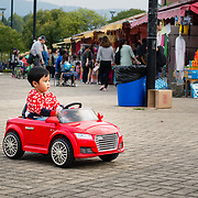 Chinese boy driving red toy car