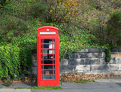 A single original old red telephone box.
