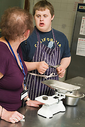 Teenaged boy with Downs Syndrome learning to cook in lesson at special school,
