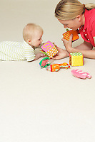Mother and child playing with toys on floor