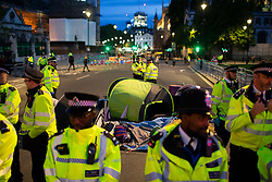 © Licensed to London News Pictures. 09/10/2019. London, UK. Police remove tents from an Extinction Rebellion roadblock in Westminster. Police continue to attempt to clear roads in Westminster on the third day of the protest.  Photo credit: George Cracknell Wright/LNP