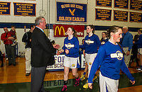 Larry Johnson from MacDonald's Corp. congratulates the Gilford girls basketball team on their championship win Thursday evening during the 42nd annual Holiday Basketball Tournament at Gilford High School.  (Karen Bobotas/for the Laconia Daily Sun)