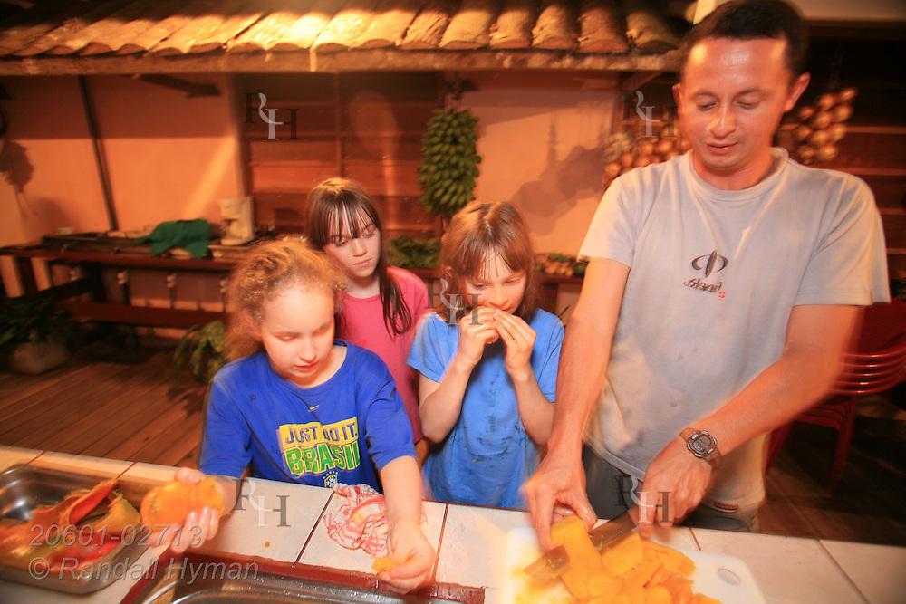 Ecoteach girls Soley Hyman (9), Kelsey Seibel (11) and Caitlin Seibel (9) eat mangos while guide Alex Alvarez Rojas prepares the fruit for blender at organic farm of Juan Bautista Castro; La Fortuna, Costa Rica.