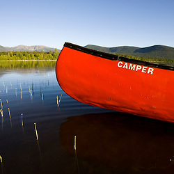 A canoe in early morning on Maine's Katahdin Lake.  Mount Katahdin is in the distance.  Near B axter State Park.