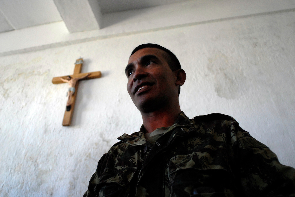 """Major Alfredo Reinado after Sunday Mass in Maubisse, East Timor,  11 June 2006. (3rd from left). Later, at a press conference in Maubisse, rebel leaders Major Alfredo Reinado and Manuel Tilman (2nd from left) announce they are planning a conference to seek ways of modifying East Timor's constitution to allow greater power for President Xanana Gusmao. Current Prime Minister Mari Alkitiri """"does not have the confidence of the people"""" said Tilman. """"Time is the most dangerous weapon"""" said Reinado."""