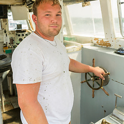 """Richard Curtis at the wheel of his lobster boat, """"Margaritaville"""" at the Friendship Lobster Co-op in Friendship, Maine."""