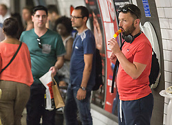 © Licensed to London News Pictures. 01/07/2015. London, UK. A man enjoys an ice lolly on a day in which commuters and tourists struggle with the intense heat on the London Underground today (01/07) on what is set to be the hottest day this decade. Photo credit : James Gourley/LNP