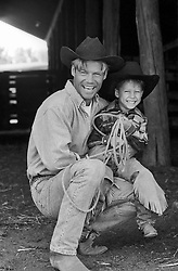 cowboy with his cowboy son in a barn
