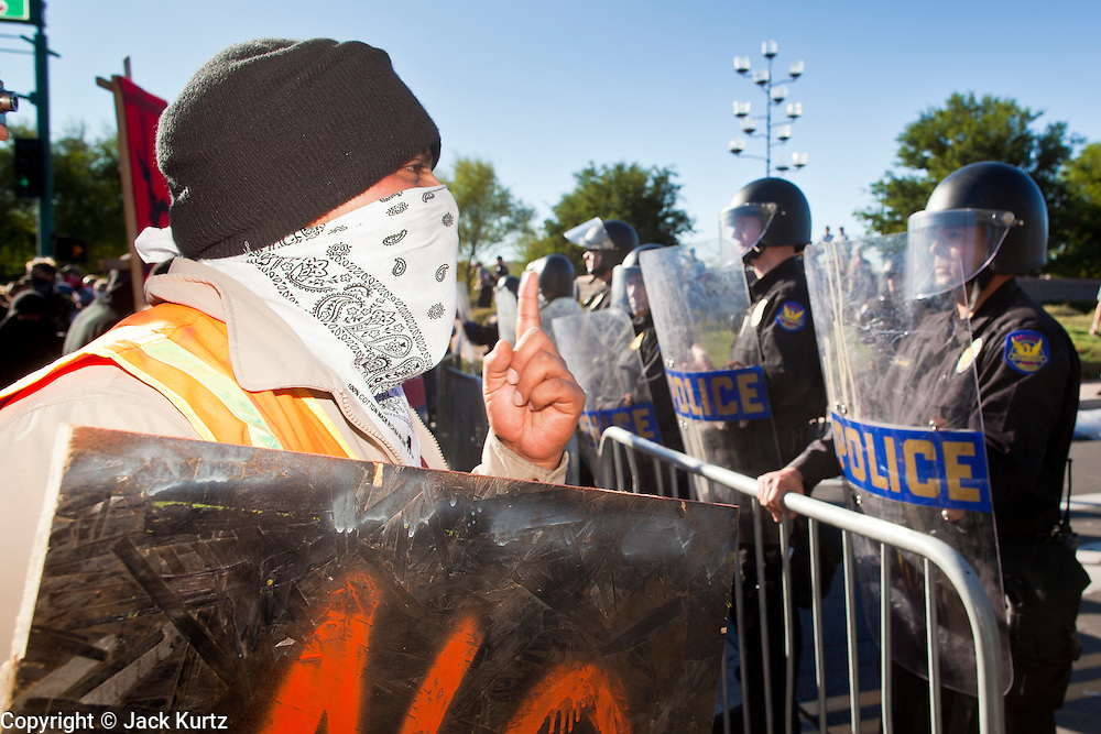 30 NOVEMBER 2011 - PHOENIX, AZ:    An anti-ALEC protester in front of the police line at the Westin Kierland Resort and Spa Wednesday. About 300 people picketed the American Legislative Exchange Council (ALEC) conference at the Westin Kierland Resort and Spa in Phoenix, AZ, Wednesday. The protesters claim ALEC, a conservative think tank, violates its tax exempt status by engaging in lobbying, a charge ALEC officials deny. Many conservative pieces of legislation, like Arizona's anti-immigration bill SB1070, originate with ALEC conferences (SB 1070 originated at an ALEC conference several years ago). Many of the protesters are also members of the Occupy movement.   PHOTO BY JACK KURTZ