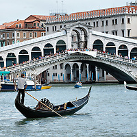 VENICE, ITALY - AUGUST 11:  A Gondola sails the Grand Canal in front of a busy Rialto bridge on August 11, 2011 in Venice, Italy. Italian heritage group Italia Nostra warned  that Venice is facing an irreversible environmental catastrophe unless visitor numbers are capped. The acceptable maximum number of tourists for Venice is 33,000. In 2011 the average number of visitors to the city daily is 60,000 that is too high for such a fragile city and is causing the gradual destruction of the lagoon ecosystem.