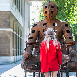London, UK - 2 September 2014: a woman looks up at  Xavier Mascaró's  installation 'Guardians'. These rusted iron warriors, nearly 10 feet high, are both imposing and placid, and are inspired by medieval armour and ancient Egyptian and Greek art. Xavier Mascaró's first UK solo exhibition will run from 3 September until 5 October at Saatchi Gallery.