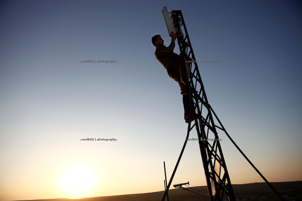 Mohammad, operator of the recently established Wi-Fi network covering Koreen, climbs up a transmission mast on a rooftop. It is the first time the village gets access to the world wide web at all. In the meantime another operater has set up a second network. Economic competition in times of uncertainty.<br />