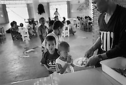 Im Gemeinschaftsaal, dem Kinderstern bekommen die Kinder nehmen die Kinder das Abendessen ein..HIN bedankt sich fuer das Essen das ihm SOMBAT ueberreicht. Provinz Lop Buri, Thailand..Dinner in the commonhouse. HIN, age 6, thanks for his plate of food, SOMBAT, age 30 one of the HIV-positive men in BAAN GERDA serves the plates to the children. Others are in line to pick up their plates. Province Lop Buri, Thailand....