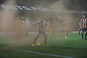 PLaying on during flare during the Sky Bet Championship match between Brentford and Wolverhampton Wanderers at Griffin Park, London, England on 29 November 2014.