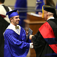 Cooper Moore walks across stage as he receives his diploma and a hand shake from Tupelo Public School District Superintendent Dr. Dearl Loden Friday night at Tupelo High School's graduation ceremony at the BancorpSouth Arena in Tupelo.