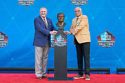 Aug 3, 2019; Canton, OH, USA; Johnny Robinson (right) and presenter Bob Thompson poses with bust of Robinson during the Pro Football Hall of Fame Enshrinement at Tom Benson Hall of Fame Stadium. (Robin Alam/Image of Sport)