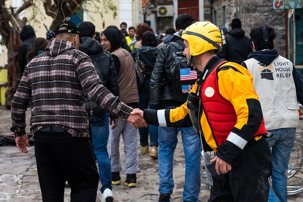 A rescue worker shakes the hand of a refugee who had just landed on the north shore of the Greek island of Lesvos in the village of Skala Skamineas, after crossing the Aegean Sea from Turkey on March 19, 2017.<br />