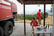 Griekenland, Amfissa, 5-7-2008Brandweermannen in midden griekenland hebben hun bluswagen langs de weg bij een kapelletje klaargezet om bij een bosbrandmelding snel ter plekke te kunnen zijn. De wagens zijn al oud, en men klaagt over de slechte staat van het materieel. In griekenland zijn op de Peloponesos en bij Athene al enkele branden geweest. Het is zeer warm, 35 tot 40 graden, en het heeft al weken niet geregend. Men is zeer waakzaam, en overal houden brandweerteams langs de berghellingen de wacht. Waar zij niet kunnen komen worden blusvliegtuigen ingezet.Foto: Flip Franssen