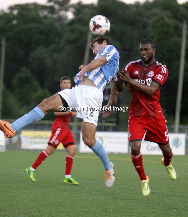 Wilmington Hammerheads FC's Steven Miller challenges Toronto FC's Ashtone Morgan Wednesday June 18, 2014 at Legion Stadium in Wilmington, N.C. (Jason A. Frizzelle)