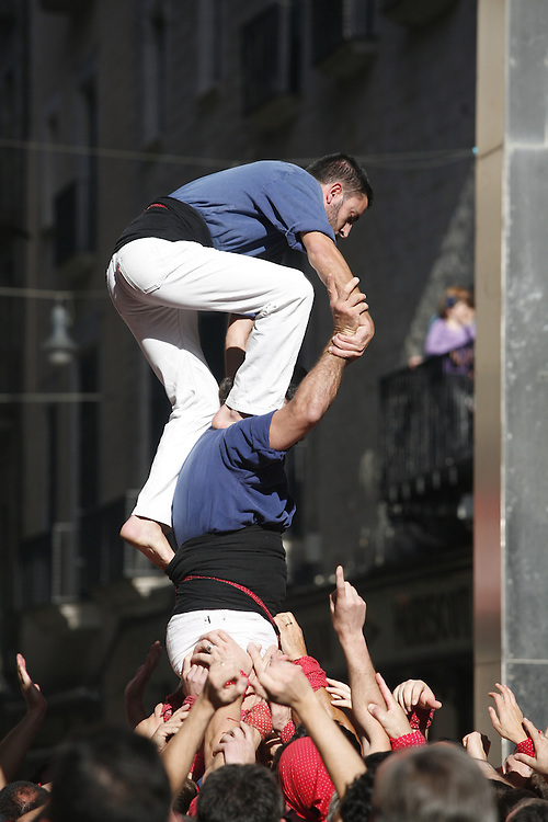 "The ""Castellers"" (human towers)  are part of a Catalan popular festivity that consists of erecting human towers of several meters of height. ""Grallers"" plays the instrument ""gralla""  to give support to the people who are constructing the tower."