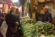 FEZ, MOROCCO - 05th MARCH 2016 - Tourists chat with a market vendor selling fresh fruit and vegetables at a market stall while grocery shopping in the old Fez Medina, Middle Atlas Mountains, Morocco.