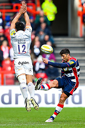 Gavin Henson of Bristol Rugby kicks as Ben Tapuai of Bath Rugby attempts a charge down - Rogan Thomson/JMP - 26/02/2017 - RUGBY UNION - Ashton Gate Stadium - Bristol, England - Bristol Rugby v Bath - Aviva Premiership.