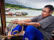 17 SEPTEMBER 2014 - SANGKHLA BURI, KANCHANABURI, THAILAND: A member of the Mon community tightens a rope used to guide a piling into place on the Mon Bridge. The 2800 foot long (850 meters) Saphan Mon (Mon Bridge) spans the Song Kalia River. It is reportedly second longest wooden bridge in the world. The bridge was severely damaged during heavy rainfall in July 2013 when its 230 foot middle section  (70 meters) collapsed during flooding. Officially known as Uttamanusorn Bridge, the bridge has been used by people in Sangkhla Buri (also known as Sangkhlaburi) for 20 years. The bridge was was conceived by Luang Pho Uttama, the late abbot of of Wat Wang Wiwekaram, and was built by hand by Mon refugees from Myanmar (then Burma). The wooden bridge is one of the leading tourist attractions in Kanchanaburi province. The loss of the bridge has hurt the economy of the Mon community opposite Sangkhla Buri. The repair has taken far longer than expected. Thai Prime Minister General Prayuth Chan-ocha ordered an engineer unit of the Royal Thai Army to help the local Mon population repair the bridge. Local people said they hope the bridge is repaired by the end November, which is when the tourist season starts.    PHOTO BY JACK KURTZ