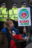 A woman and her baby sitting in front of a line of police officers at the North Gate of Her Majesty's Naval Base, Clyde, Faslane, Scotland, during a blockade by around 150 people protesting against the Trident nuclear missile system. The protestors managed to shut down the base, preventing workers, contractors and naval personnel from accessing the site. A decision was due to be made by the UK government in 2016 whether to replace the Trident submarine system.