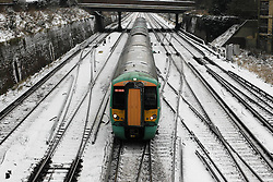 © Licensed to London News Pictures. 19/01/2013, London, UK.  A train passes along snow covered track in Croydon, South London, Saturday, Jan. 19, 2013. More cold weather and snow are expected over the coming days. Photo credit : Sang Tan/LNP