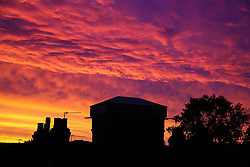 © Licensed to London News Pictures. 07/10/2019. London, UK. Rooftops and trees are silhouetted against a colourful autumn sunrise in Haringey, north London. Photo credit: Dinendra Haria/LNP